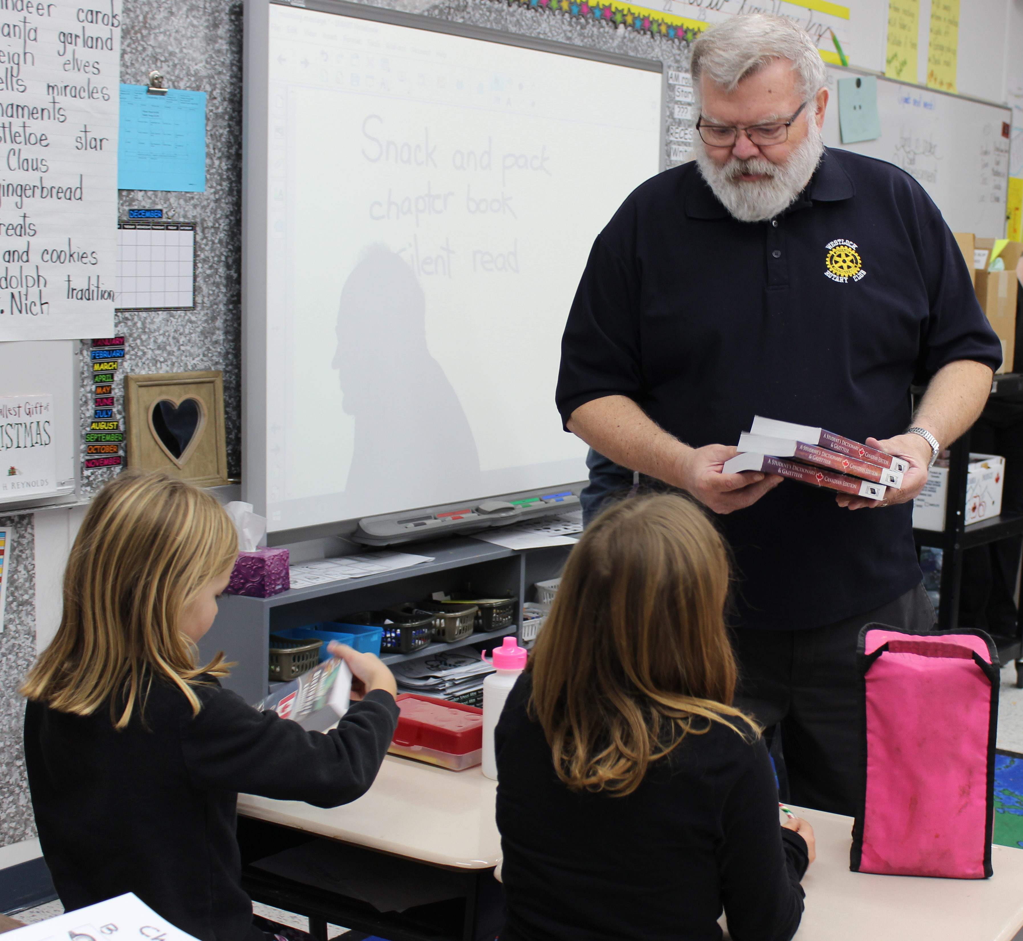 Ken Ebeling with Westlock Rotary Club hands out dictionaries to grade 3 WES students