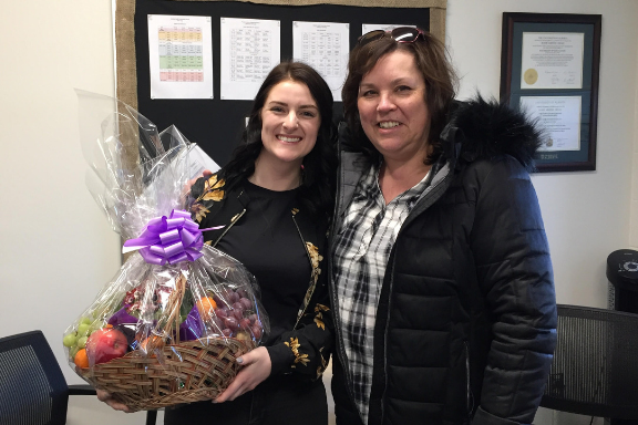 Teacher Ariana Sterling and Trustee Jackie Comeau with gift basket